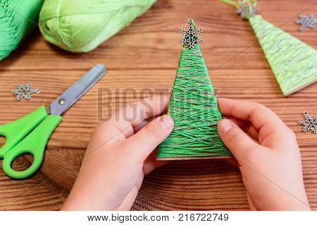 Child is holding a Christmas tree decoration in his hands. Child is showing a Christmas tree decoration. Easy recycled crafts and projects for kids. Christmas decorations on a wooden table