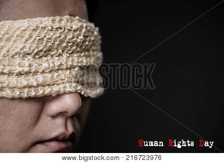 Closeup of a young woman with a blindfold in her eyes. Concept of censorship freedom of speech freedom of press. International Human Right day.