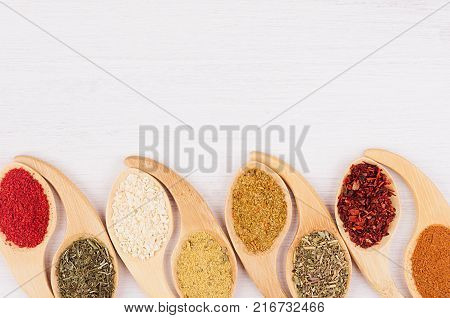 Multicolored asian spices in quaint spoons on white wooden background. Top view closeup.