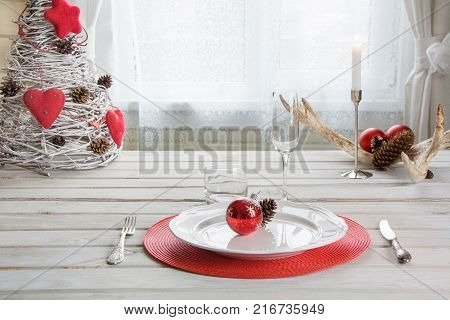 Holiday Table Place Setting With White Dishware, Cutlery, Silverware And Red Decorations On White Wo