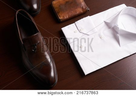 Mans fashion and accessories, set of brown leather shoes, purse, belt, white shirt and dark trousers on wooden background
