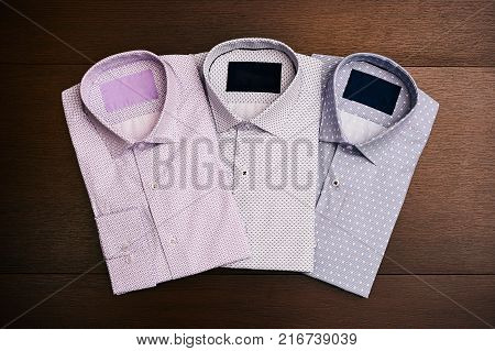 A set of 3 men's shirts on wooden background, top view. Men's fashion
