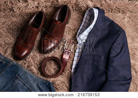 Classic men's clothes such as dark suit jacket with light shirt, jeans trousers, brown leather shoes, belt and wallet on soft carpet background.