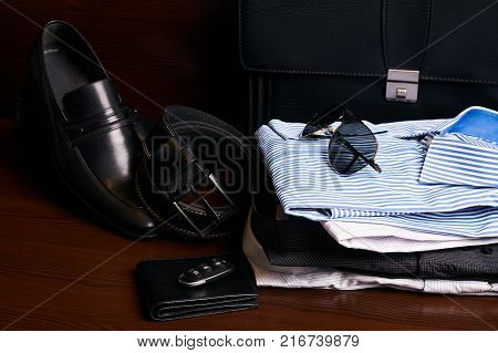 Set of mans fashion clothing and business accessories, black leather suitcase, shoes, belt, purse, glasses, shirts and car keys on wooden background. Men's fashion, close-up