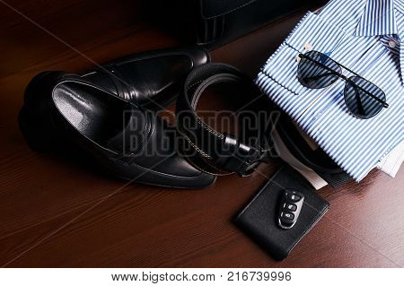 Set of men's business clothing, black leather suitcase, shoes, belt, purse, glasses, shirts and car keys on wooden background. Men's casual clothes and fashion accessories, top view.