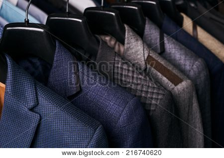 Mens suits in different colors hanging on hanger in a retail clothes store, close-up