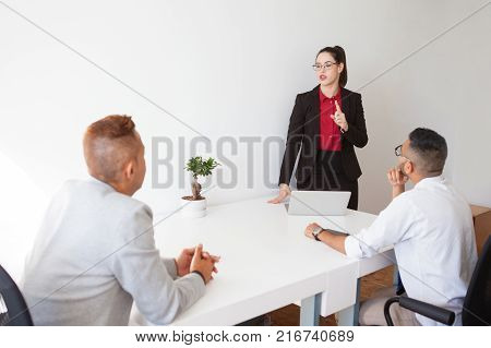 Confident lady boss conducting staff meeting and explaining tasks to colleagues. Serious confident businesswoman giving advice at meeting. Presentation concept