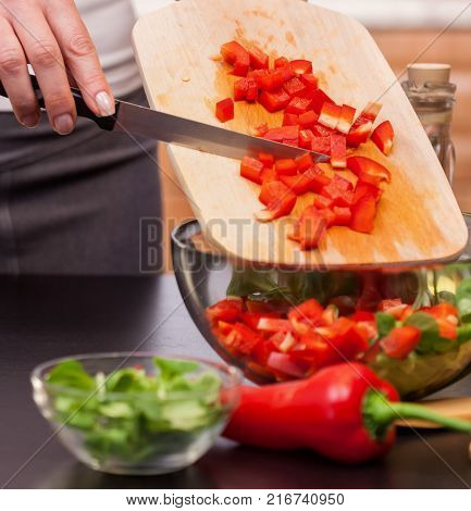 Making a vegetable salad - woman chopping red peppers putting the pieces in a bowl