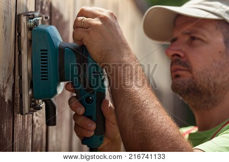 Worker using a vibrating sander machine to scrap old paint from wooden fence - closeup