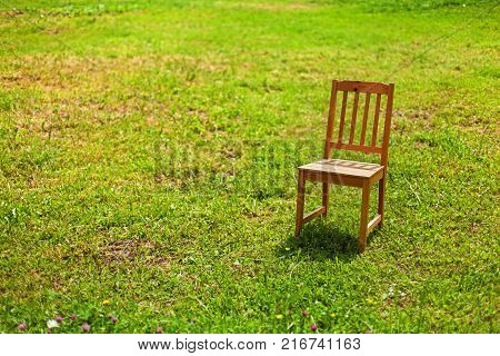Solitude of a chair on the grass in bright sunlight