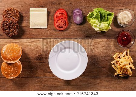 Ingredients to build the perfect hamburger - top view of wooden table and empty plate in center for copy space