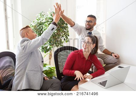 Happy young colleagues celebrating success after concluding deal. Excited male managers giving high five as symbol of good job. Achievement concept