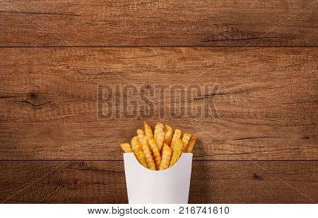 French fries in paper bag on the brown wooden table - large copy space