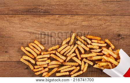 Lots of french fries spilled on the table from paper holder bag - food background with copy space