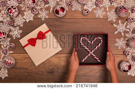 Christmas gift box inside seasonal decorations frame - child hands holding present with candy cane forming heart shape