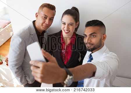 Positive multiethnic business experts making selfie on smartphone. Ambitious young colleagues photographing themselves against wall. Social media concept