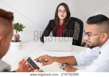 Serious confident female executive with laptop at meeting and looking at camera. Ambitious successful lady boss running business. Leader concept