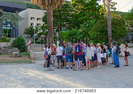 BUDVA MONTENEGRO - SEPTEMBER 5 2017: Group of tourists is near ancient necropolis and listens to guide in popular resort town of Budva Montenegro