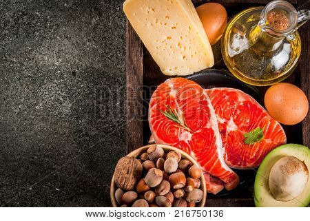 Healthy organic food. Products with healthy fats. Omega 3 omega 6. Ingredients and products: trout (salmon) olive oil avocado nuts cheese eggs. On dark stone table. Copy space top view