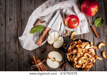 Homemade sun-dried organic apple slices crispy apple chips on an old rustic wooden table with fresh apple and cinnamon. Copy space top view
