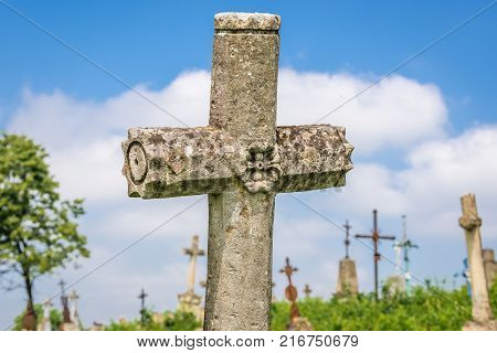 Stone cross on abandoned Catholic cemetery near Chervonohorod Castle ruins in Ukraine