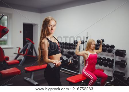 Dumbbells. Girls are engaged in a group, a body of bodybuilding with dumbbells. Elbow bending at the elbow
