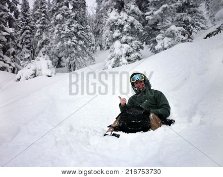 Young man sitting from powder snow. Riding with snowboard from powder snow hill or mountain.