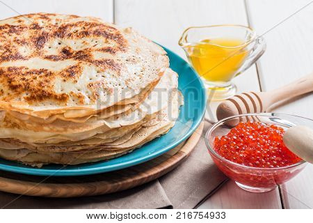 Stack of yeast pancakes, traditional for Russian pancake week witn red cavier and honey