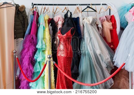 Many ladies evening gown long dresses on hanger in the dress rent shop for the wedding day or photo session. Dresses rental concept. Selective focus. Ball gown rental concept