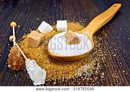 Sugar brown and white in cubes, granulated in a spoon and crystal on a stick against the background of a wooden board