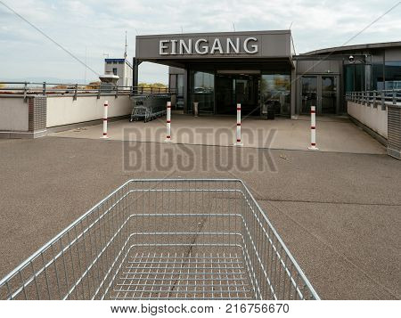 Supermarket cart in front of the entrance with Eingang translated as Entrance in german city