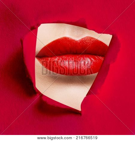 Beautiful plump lips of red color peep into the slit of red paper. Advertising. Make-up concept.