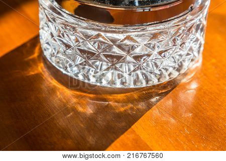 Bottom of clear drinking glass on wooden table with morning light showing cast shadow and refraction good for relax or home related concept