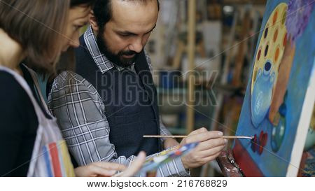 Skilled artist teacher showing and discussing basics of painting to student at art-class indoors