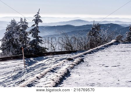 mountain ranges panorama with frozen trees snow covered road and clear sky from Lysa hora hill in Moravskoslezske Beskydy mountains in Czech republic during really cold winter day
