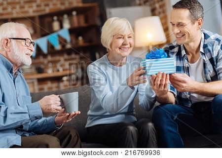 Gift with love. Cheerful young man giving a birthday present to his happy elderly mother while his father sitting next to them and drinking coffee