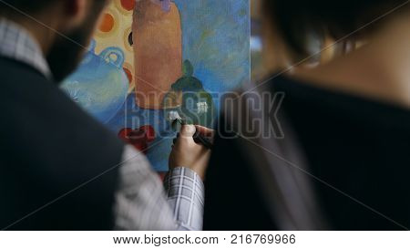Back view of Skilled artist man teaching and showing young woman the basics of painting in art studio