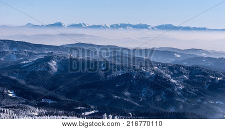 view to Krivanska Mala Fatra mountain range with nearest hills of Beskids mountains from Lysa hora hill in Moravskoslezske Beskydy mountains in Czech republic during winter day with clear sky