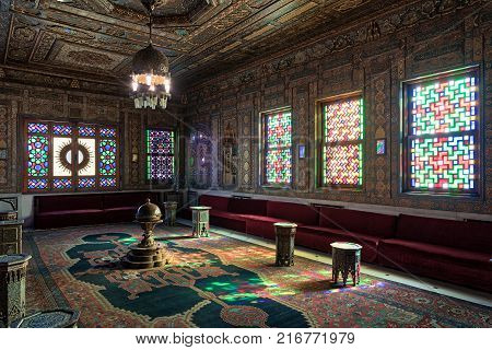 Cairo Egypt - December 2 2017: Manial Palace of Prince Mohammed Ali. Syrian Hall with ornate wooden wall and ceiling windows with colored stained glass and Ottoman Empire logo old ornate chandelier red couches tea tables and ornate carpet