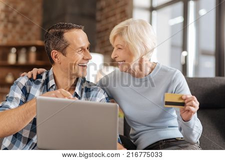 Making decisions. Cheerful elderly lady and her young son doing online shopping and discussing the purchases while the woman holding a bank card