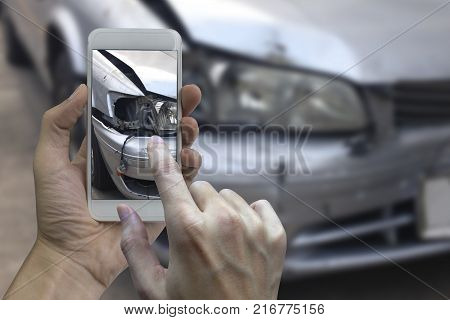 Hand holding smart phone take a photo at The scene of a car crash car accident for insurance.