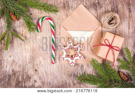 Christmas decorations with fir tree gift box candy cane painted gingerbread and letter. Preparing for Christmas. Letter and gift. Top view.