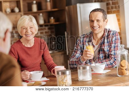 Mood-boosting conversation. Pleasant upbeat family sitting at the kitchen counter, having breakfast and talking to each other while exchanging smiles
