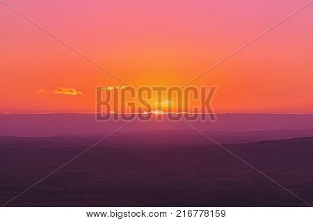 A warm pink and orange sunset landscape, with the sun setting over UK Shropshire rural countryside.