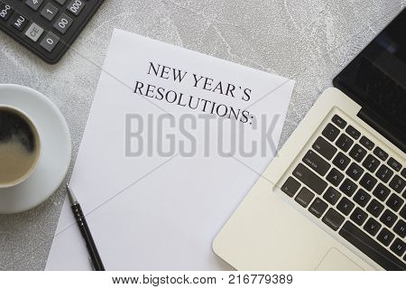 New Year's resolutions paper, laptop, stationary on a light concrete background, top view