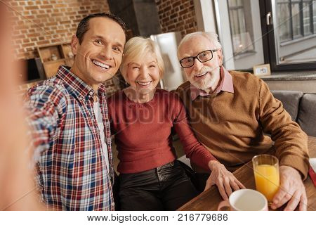 Greatest moments. Upbeat family consisting of an adult son and his senior parents sitting at the kitchen table and taking selfies together