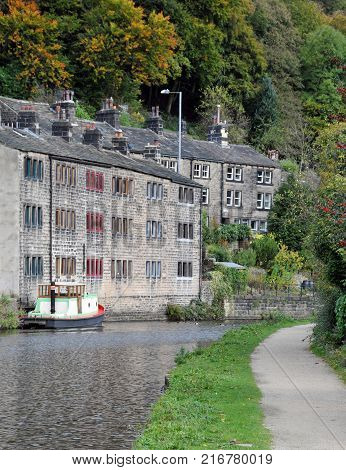 the rochdale canal at hebden bridge with towpath boat and stone houses