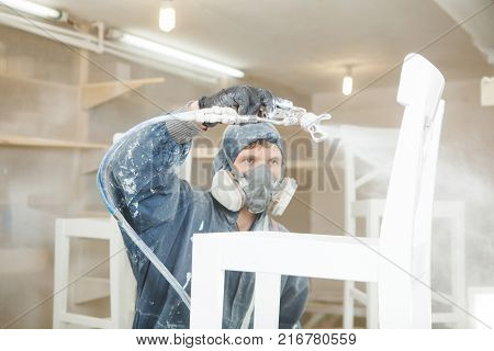 Man painting chair into white paint in respiratory mask. Application of flame retardant ensuring fire protection, airless spraying device.