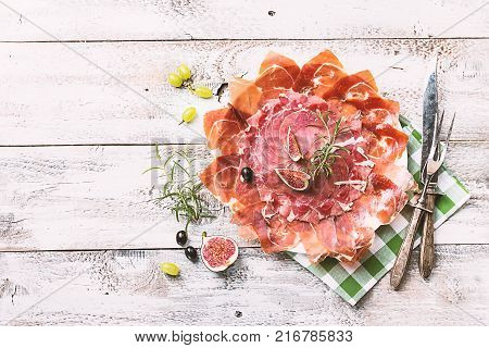 Sliced jamon on white plate. Parma ham, hamon on wooden background with fig and grapes with copy space, top view. Jamon Serrano, Iberico. Traditional Spanish ham