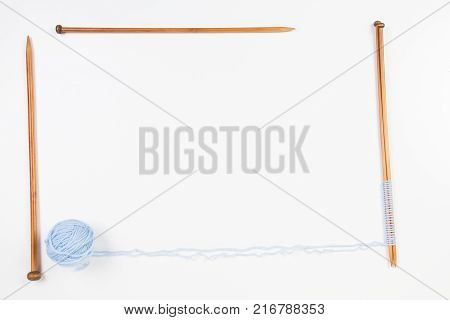 Knitting needles and blue yarn ball frame on white background. Top view, copy space for text